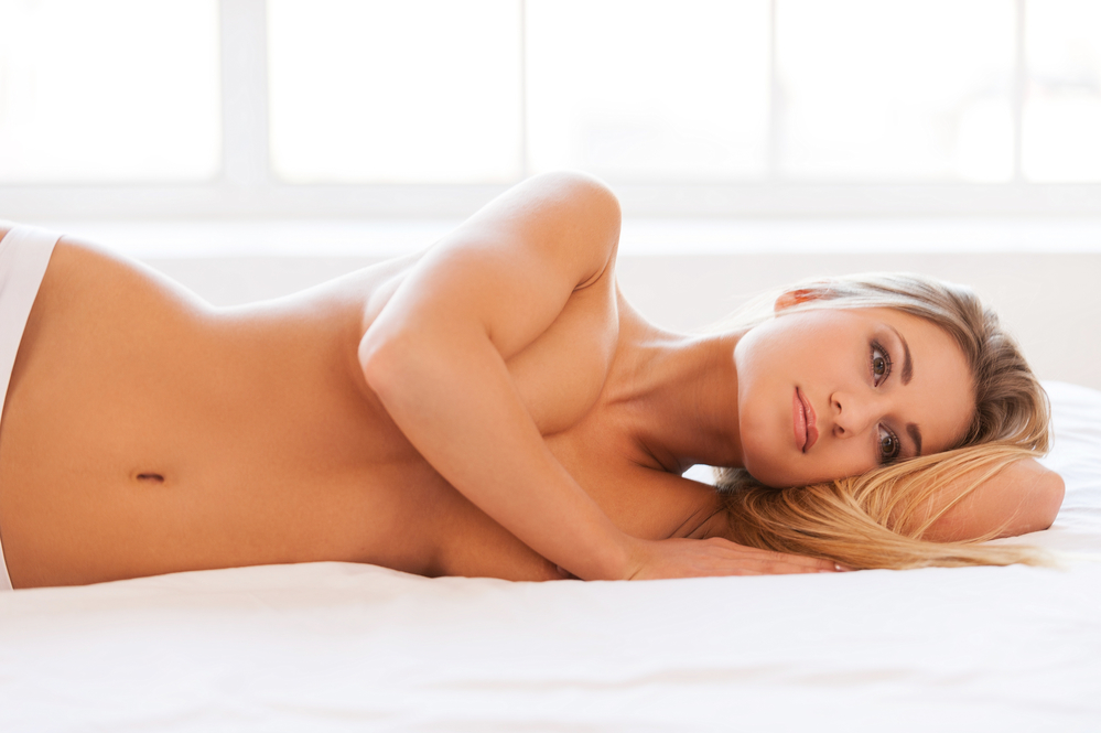 Woman lying topless covering breasts with arms on white bed