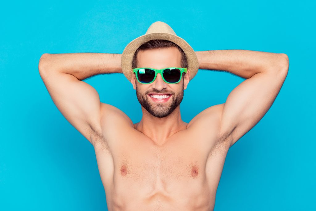 Attractive, cheerful, manly, stunning, funny man in glasses and hat holding hands behind the head, showing his shaven armpits on holidays, enjoying sunshine, taking sunbath over blue background
